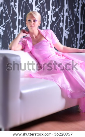 Young woman in pink dress resting on a sofa. - stock photo