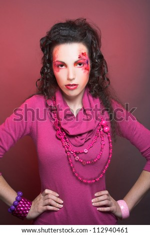 Young woman in pink dress with artistic visage with hearts