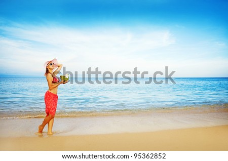 Young woman in pink swimsuit with coconut cocktail on the beach, bali - stock photo