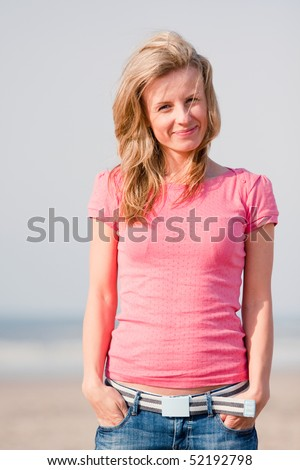 Young woman in pink t-shirt and jeans standing on sea shore. Sunset light