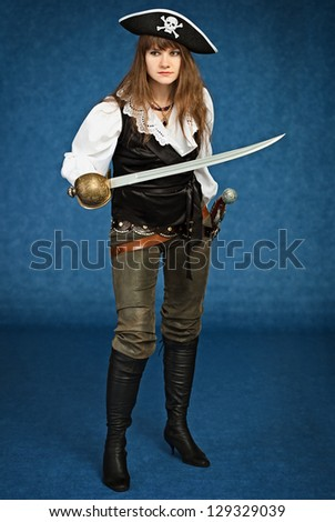 Young woman in pirate suit with sabre on blue background