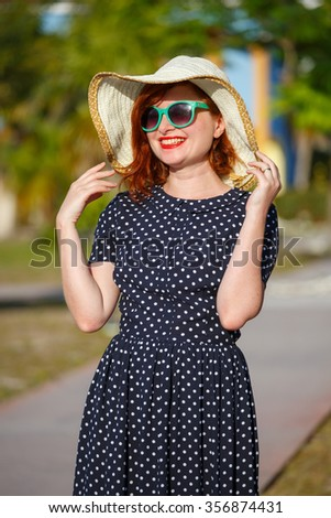 Young woman in polka-dot dress and straw hat on background of the palms - stock photo