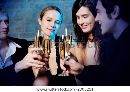 Young woman in projector beam, celebrating with friends great life event at a party in nightclub - stock photo