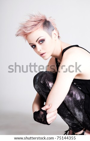 Young woman in punk attire bends over to hug her legs while looking into the camera. Vertical shot. - stock photo