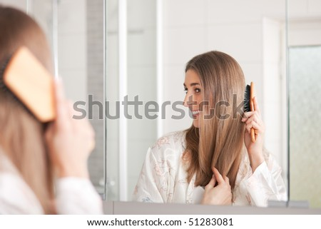 Young woman in pyjama brushing her long dark-blond hair after getting up in the morning - stock photo
