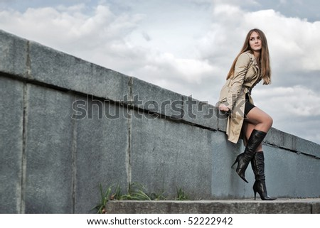 Young woman in raincoat sitting at the railing. - stock photo