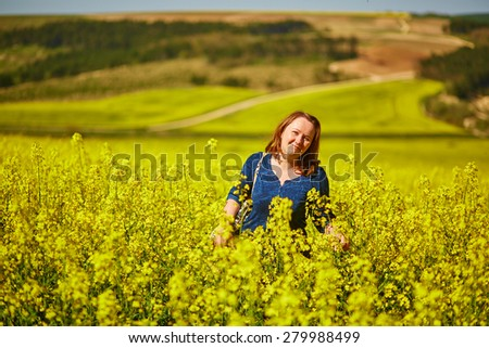 Young woman in rapeseed fields in full bloom in Burgundy, France - stock photo