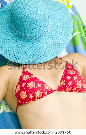 Young woman in red bikini sunbathing with blue sun hat covering her face