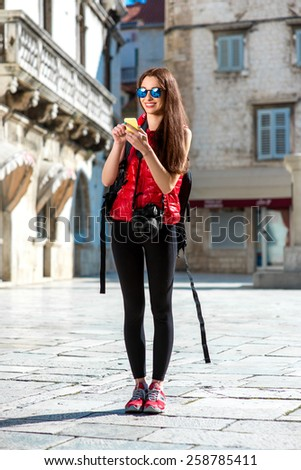 Young woman in red clothes with smart phone traveling in the old city center. Traveling application concept - stock photo