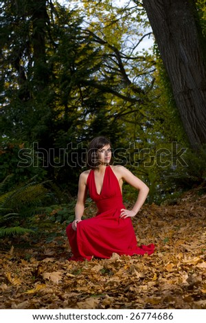 Young Woman in red dress is surrounded by leaves in the forest - stock photo