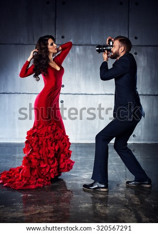 Young woman in red dress posing to man photographer. Elegant evening clothing. - stock photo
