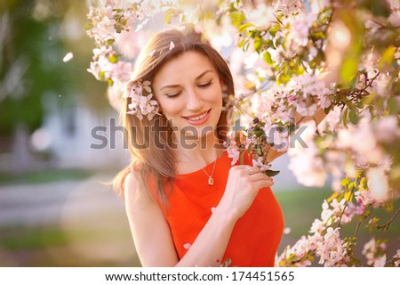 Young woman in red dress standing among blossom trees during sunny day  and wiping her nose. Girl with runny nose, having allergy and holding a tissue next to her face. - stock photo