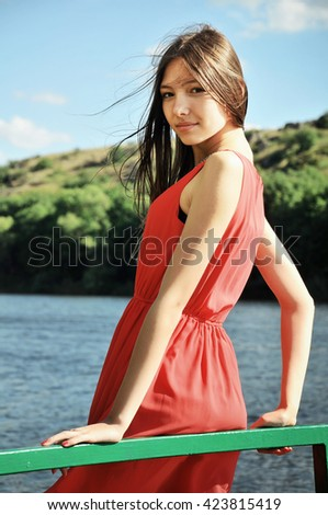 Young woman in red dress standing at the river - stock photo