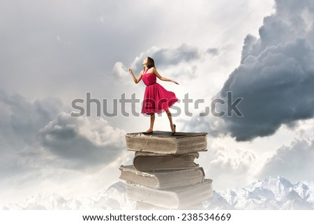Young woman in red dress standing on pile of books - stock photo