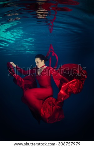 Young woman in red dress underwater with reflection - stock photo