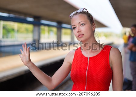 Young woman in red dress waiting on the platform of a railway station for their train. to arrive.
