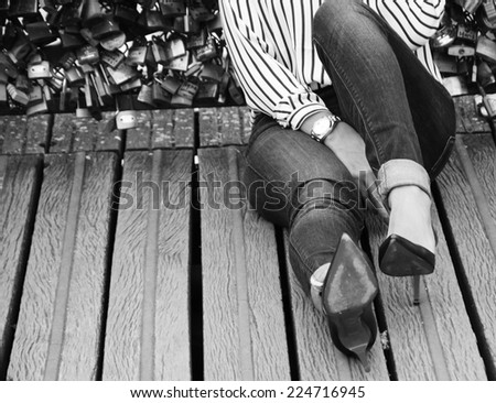 Young woman in red high heel shoes sitting on Love locks bridge in Paris. Retro aged photo. Black and white.  - stock photo