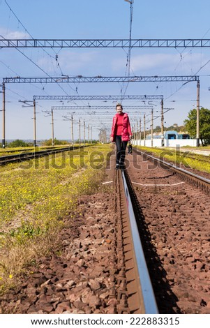 Young woman in red jacket goes away on railroad tracks at the camera - stock photo