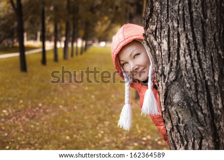 Young woman in red jacket looks out of the autumn park tree