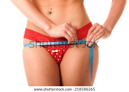 Young woman in red lingerie measuring its volume. Chest, waist, hips. Isolation on a white background. - stock photo