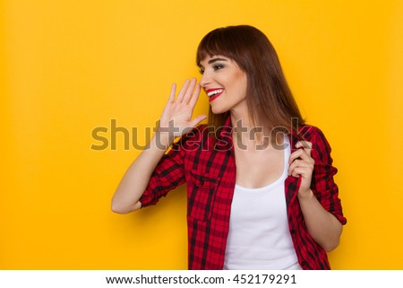 Young woman in red lumberjack shirt holding hand close to the mouth, looking away and talking. Waist up studio shot on yellow background.