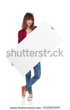 Young woman in red lumberjack shirt, jeans and brown sneakers holding white blank placard and looking at camera. Front view. Full length studio shot isolated on white. - stock photo
