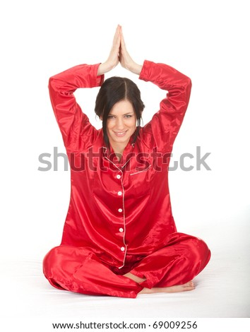 young woman in red pajamas meditating in lotus position