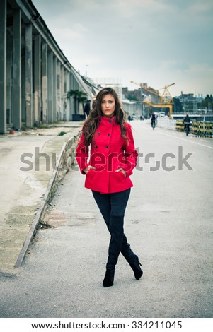 young woman in red short coat, pants and high heels boots,  outdoor on  street,  full body shot  - stock photo