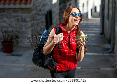 Young woman in red sportswear looking where to go with smart phone traveling in the old city center. Traveling application concept - stock photo