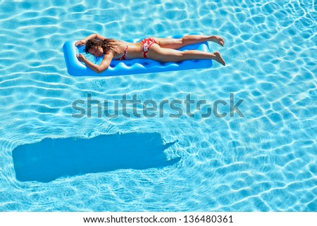 Young woman in red swimsuit bakes lying on inflatable mattress in pool - stock photo