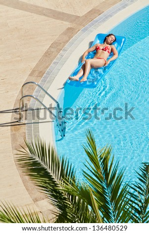 Young woman in red swimsuit bakes lying on inflatable mattress on water near to edge of pool - stock photo