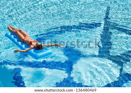 Young woman in red swimsuit bakes with arms outstretched on inflatable mattress in pool - stock photo