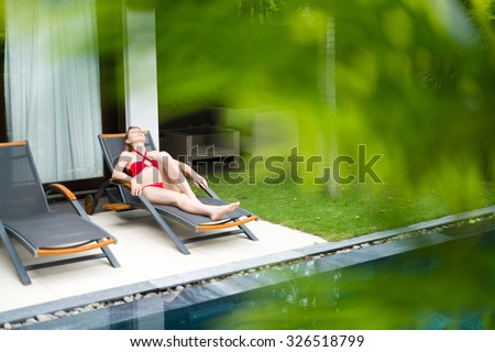 Young woman in red swimsuit relaxing on chaise longue near pool. Blurred palm tree leaves in foreground. Comfortable sunbathing in hotel area. Summer vacation on tropical resort.
