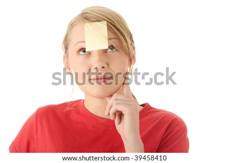 Young woman in red tshirt with yellow sticky note on forehead. Isolated. - stock photo