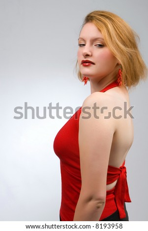 Young woman in red watching over her shoulder