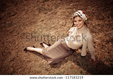 young woman in retro look clothes outdoor shot sit on dry grass - stock photo