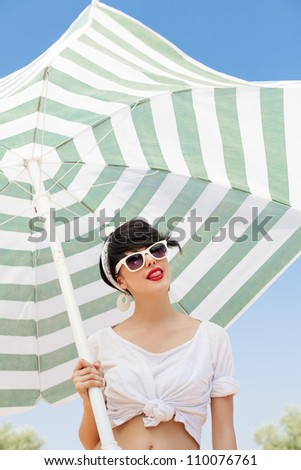 young woman in retro style by color umbrella - outdoors - stock photo