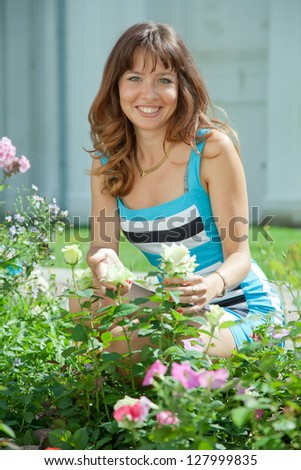 young woman in roses plant at garden - stock photo