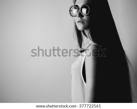 Young woman in round glasses. Black and white. High contrast - stock photo