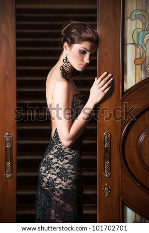 Young woman in royal interior. Standing at the door. - stock photo