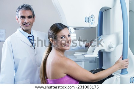 Young woman in 30s undergoing scan at mammography machine with happy male doctor. Health concept. - stock photo
