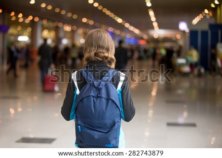 Young woman in 20s with backpack walking in airport terminal, wearing casual style clothes, rear view - stock photo