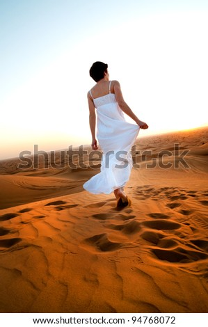 young woman in sandy desert at sunset - stock photo
