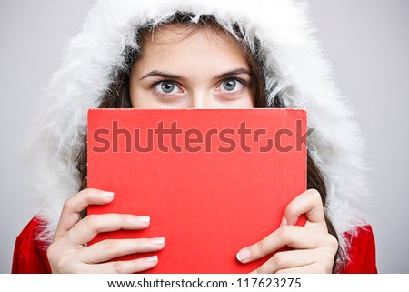 Young woman in Santa Claus clothing with banner - stock photo