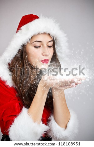 Young woman in santa cloth blowing snow from hands - stock photo