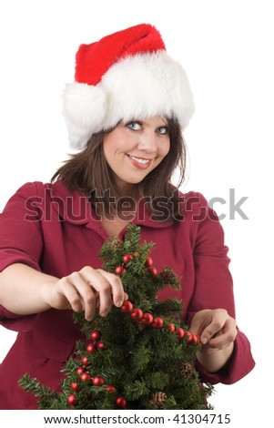 Young woman in Santa hat decorates a Christmas tree with red beads; isolated on a white background. - stock photo