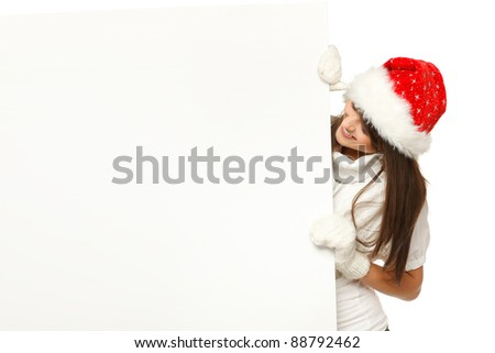 Young woman in Santa hat holding a blank billboard, looking out from behind it, over white background - stock photo