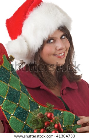Young woman in Santa hat holds a Christmas stocking near a decorated Christmas tree: close-up and isolated on a white background. - stock photo