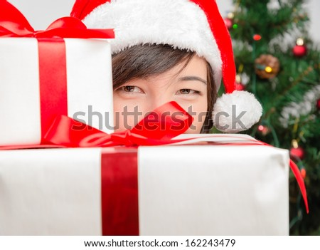 Young woman in santa hat looks out from behind gift box - stock photo
