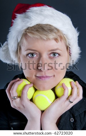 Young woman in Santa's hat holding tennis balls - stock photo